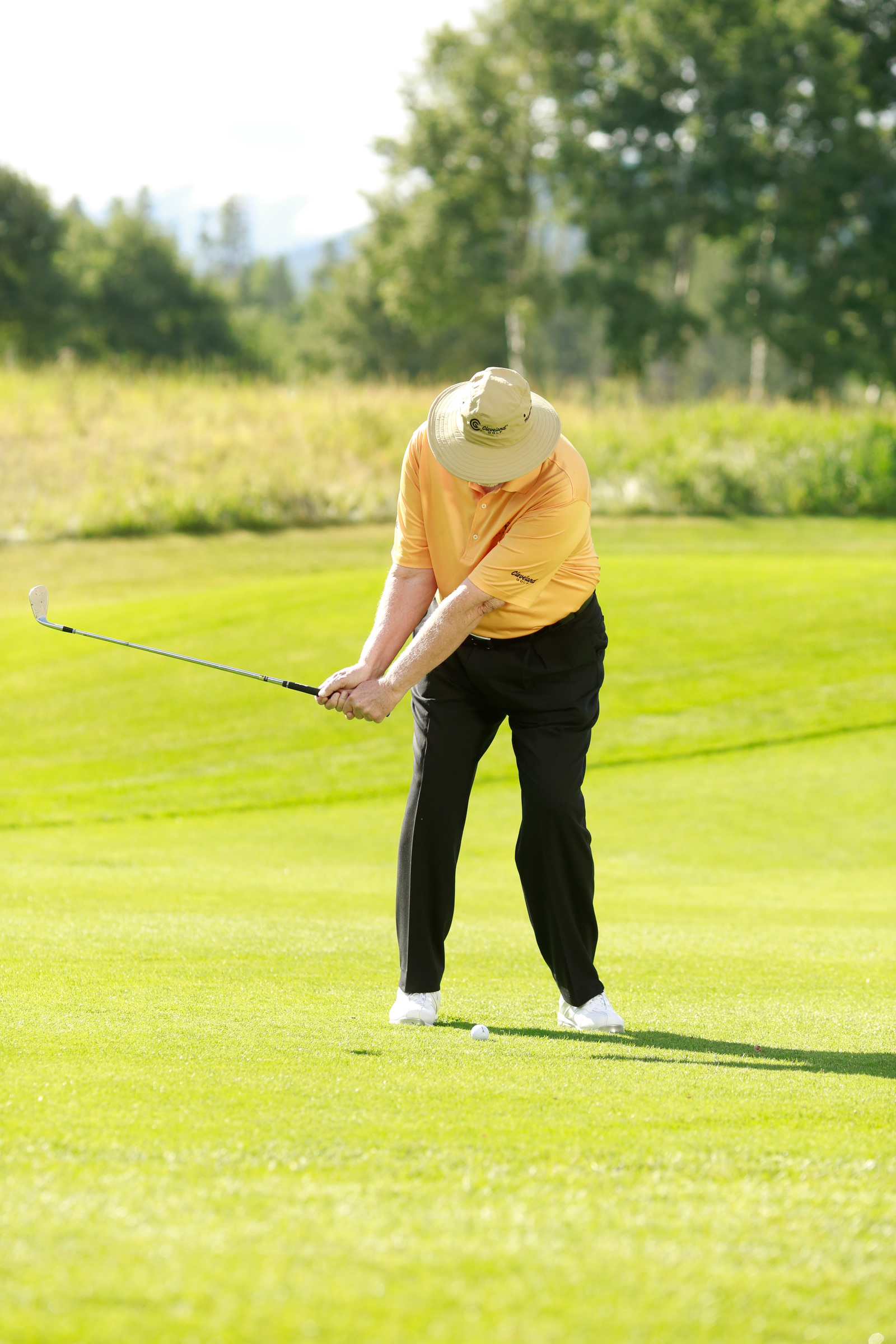 Backswing keys: Keep your wrists slightly hinged and stop your hands just below your waistline, with your upper and lower body in sync.