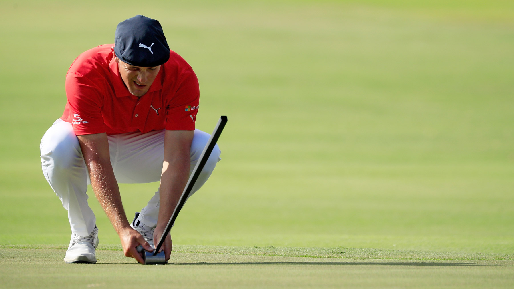 Bryson DeChambeau lines up a putt before employing his side-saddle putting technique at the 2017 Sony Open.