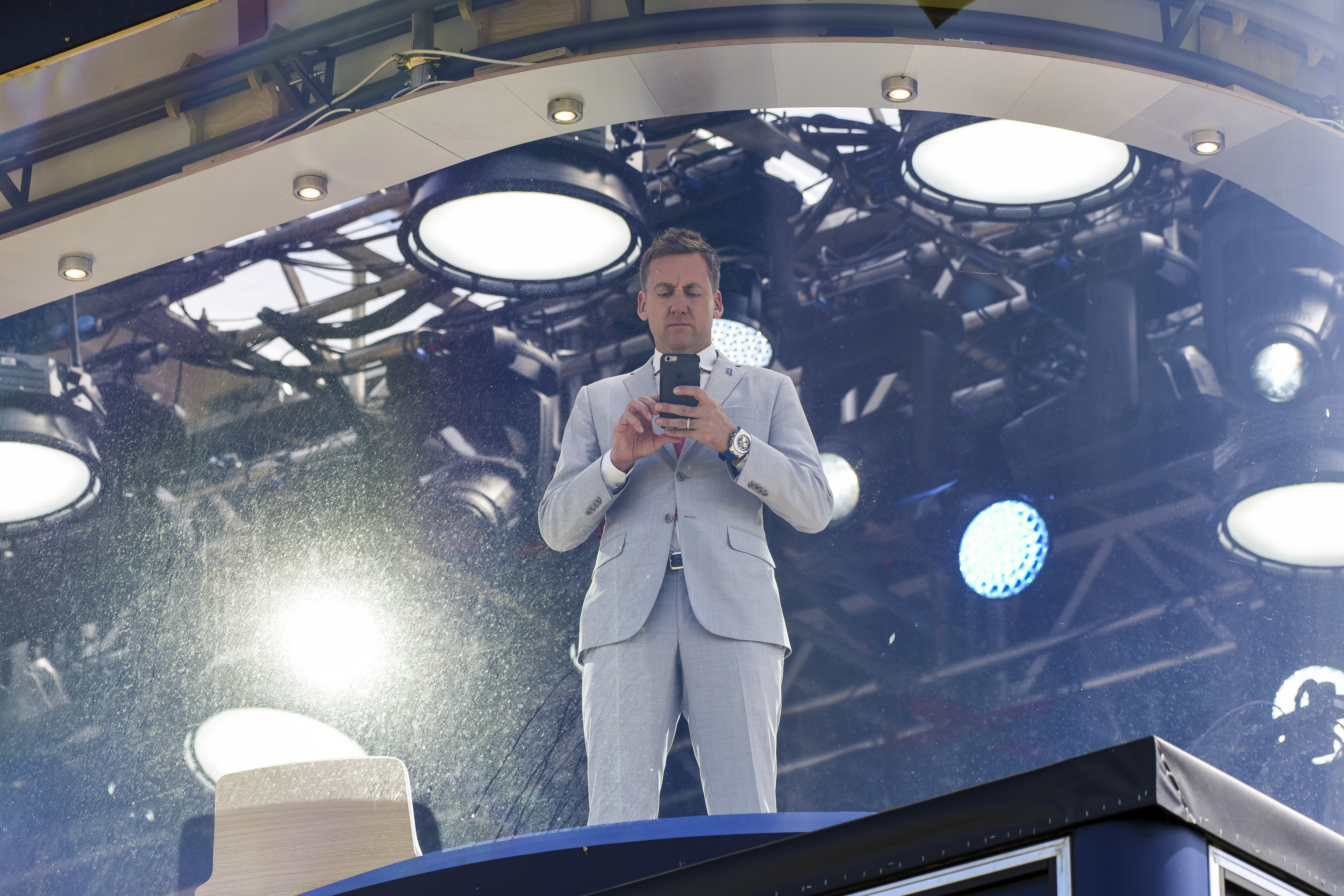 Ian Poulter takes pictures with his Apple iPhone from the Sky Sports television broadcast booth during the first round on day one of the 145th Open Championship at Royal Troon.