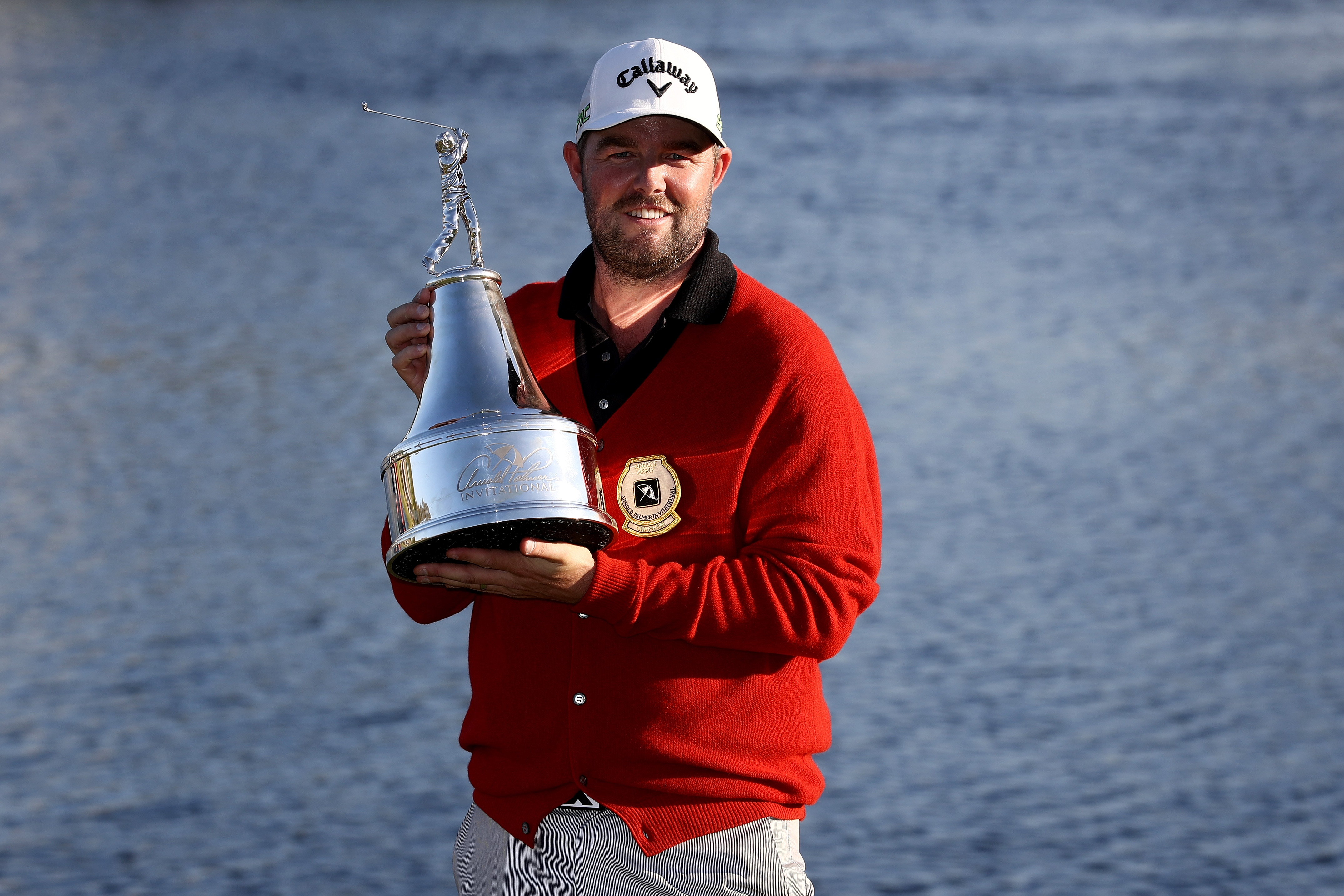 Marc Leishman poses with the red cardigan after winning the Arnold Palmer Invitational.