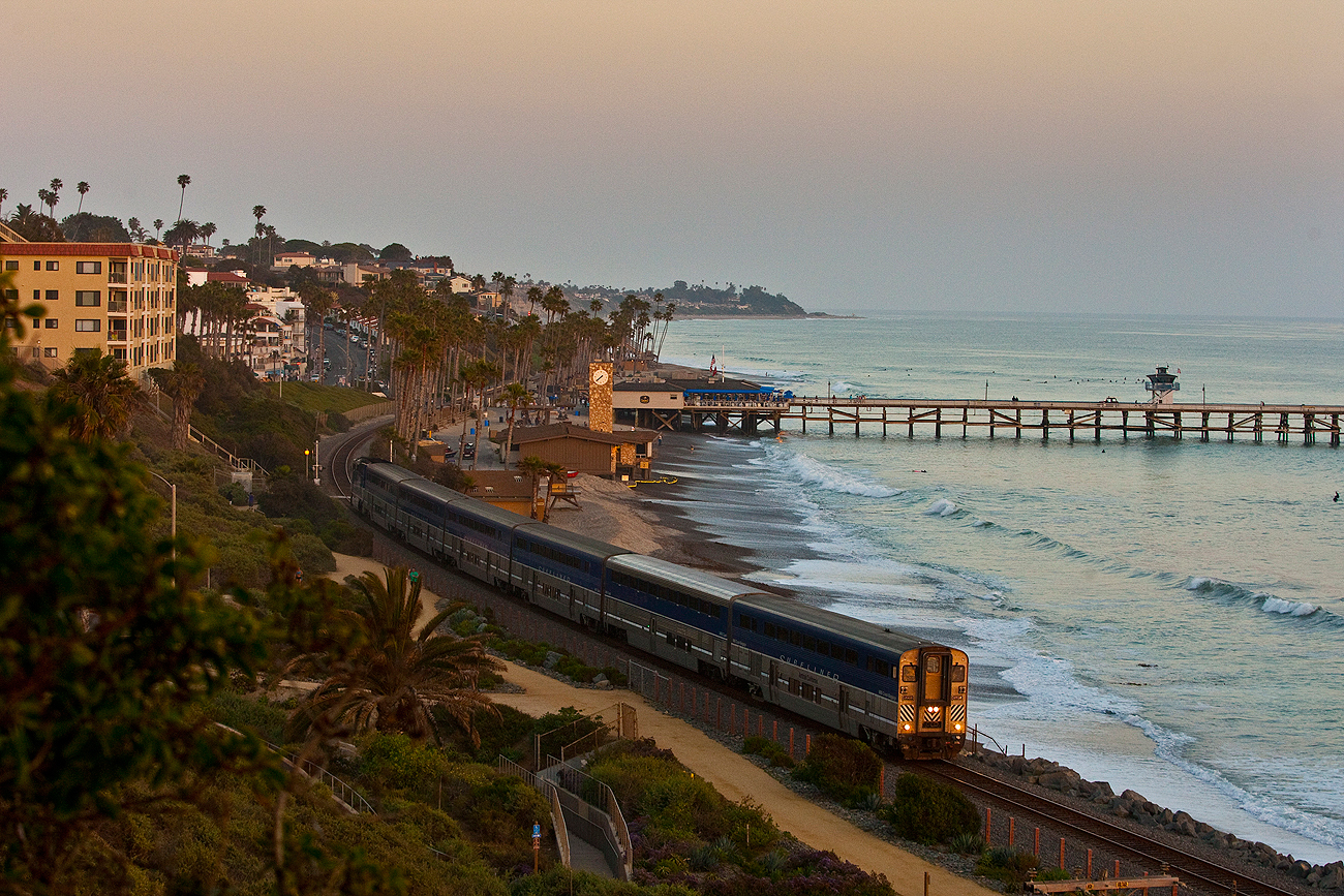 The Amtrak Pacific Surfliner train travels past the the San Clemente pier at sunset.