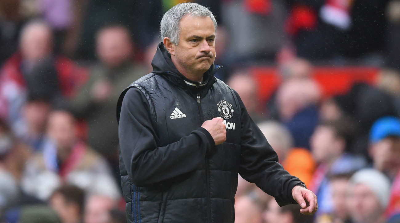 Jose Mourinho points to the crest after Manchester United beats Chelsea