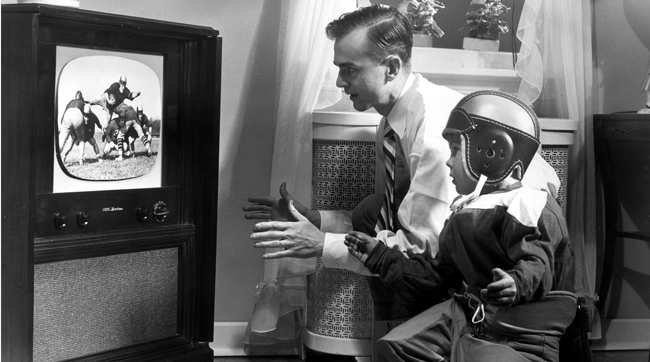 A father and son watching football circa 1955.