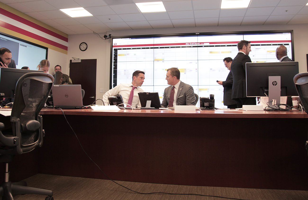 Shanahan and Lynch discuss strategy while Marathe (left) works the phones and Peters and Mayhew (right) review the board.