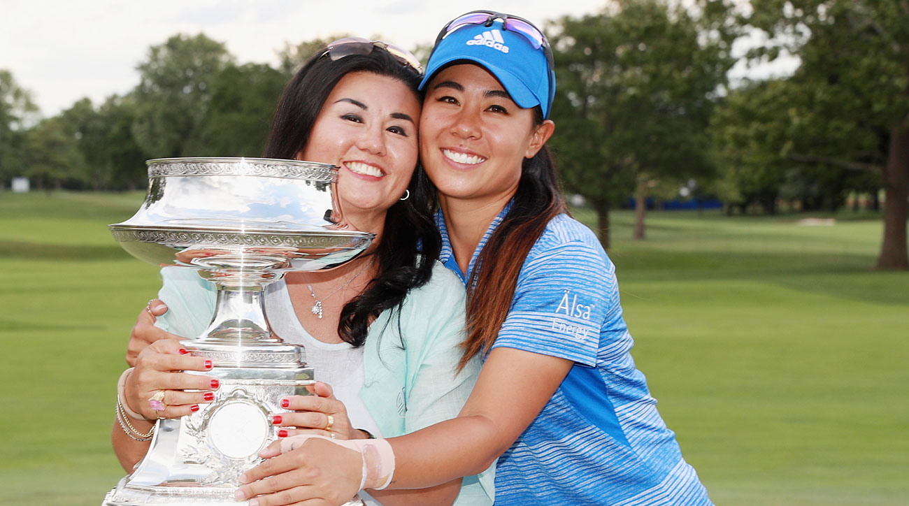 Danielle Kang and her mother pose with the KPMG Women's PGA trophy after her win at Olympia Fields.