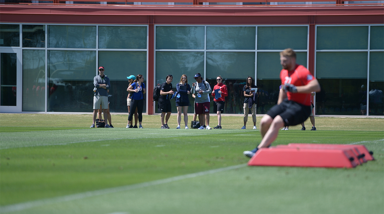 Katie Sowers (third from left, in black) participates in the NFL Pro Player Combine as a scout.