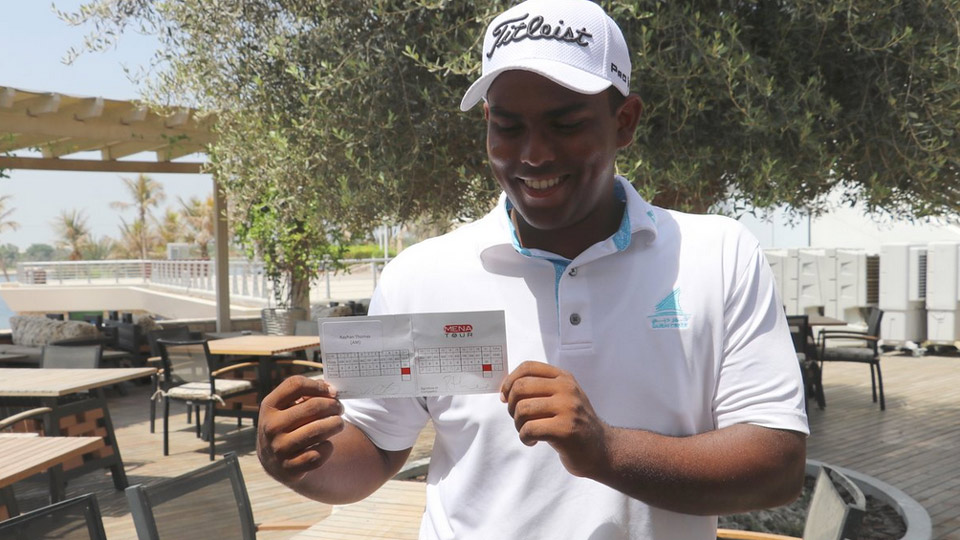 Rayhan Thomas poses with his record-tying scorecard, which features nine consecutive birdies.
