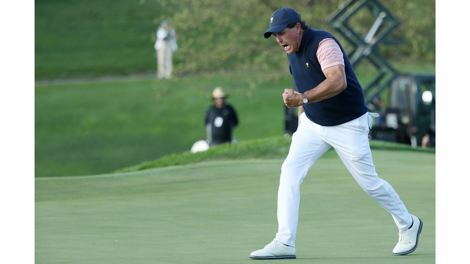Phil Mickelson celebrates his clutch, match-winning birdie putt on the 18th hole on Friday evening.