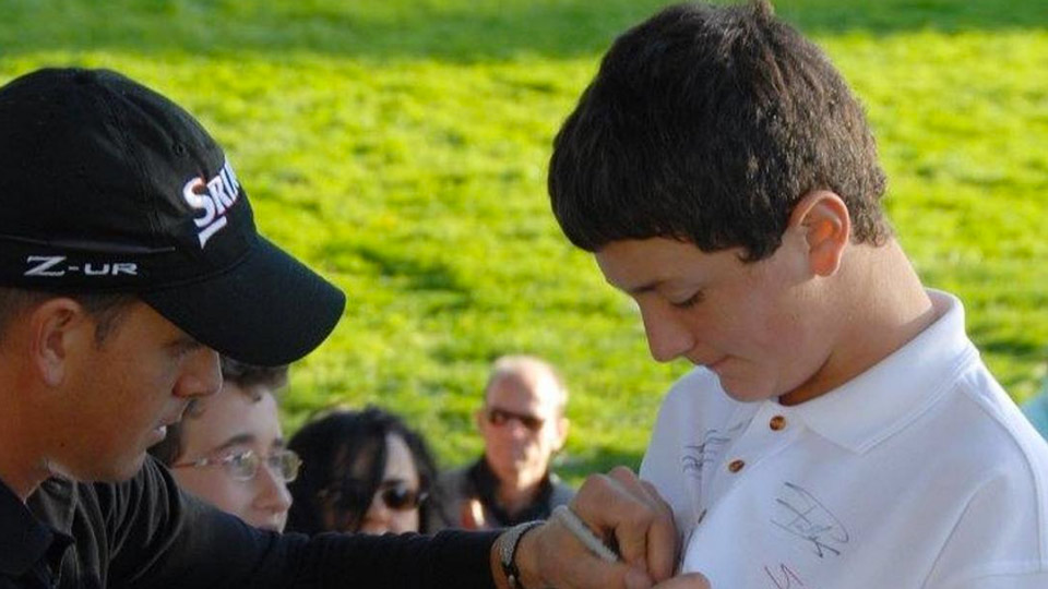 A young Jon Rahm receives an autograph from Henrik Stenson.