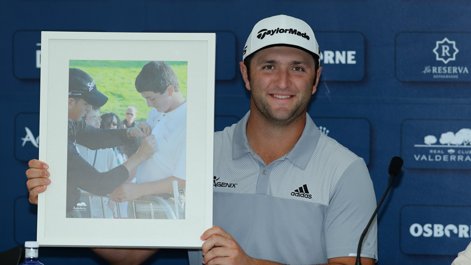 Jon Rahm holds a framed photograph of himself receiving an autograph from Henrik Stenson over ten years ago.