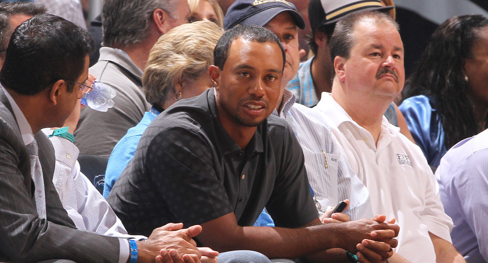 Tiger Woods sits courtside for the Orlando Magic's season opener against the Washington Wizards in 2010.