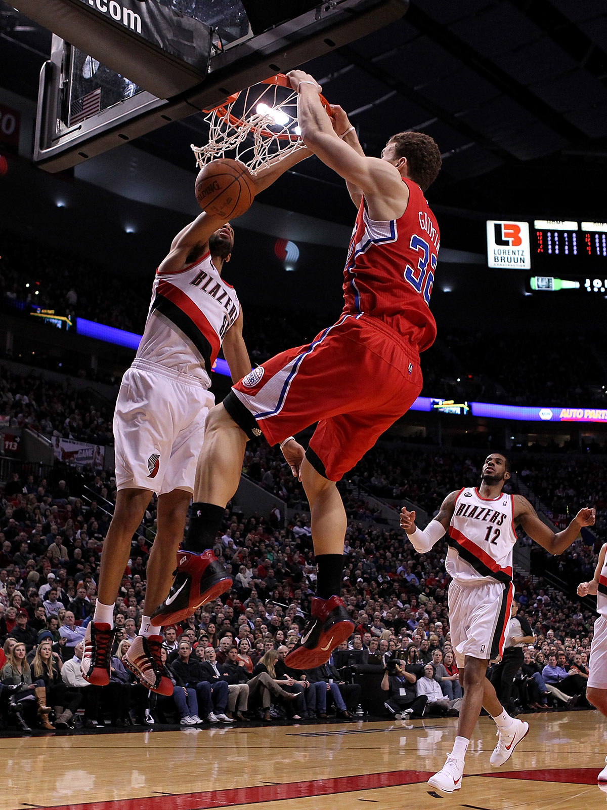 Clippers star Blake Griffin finishes a dunk with two hands over Nicolas Batum.