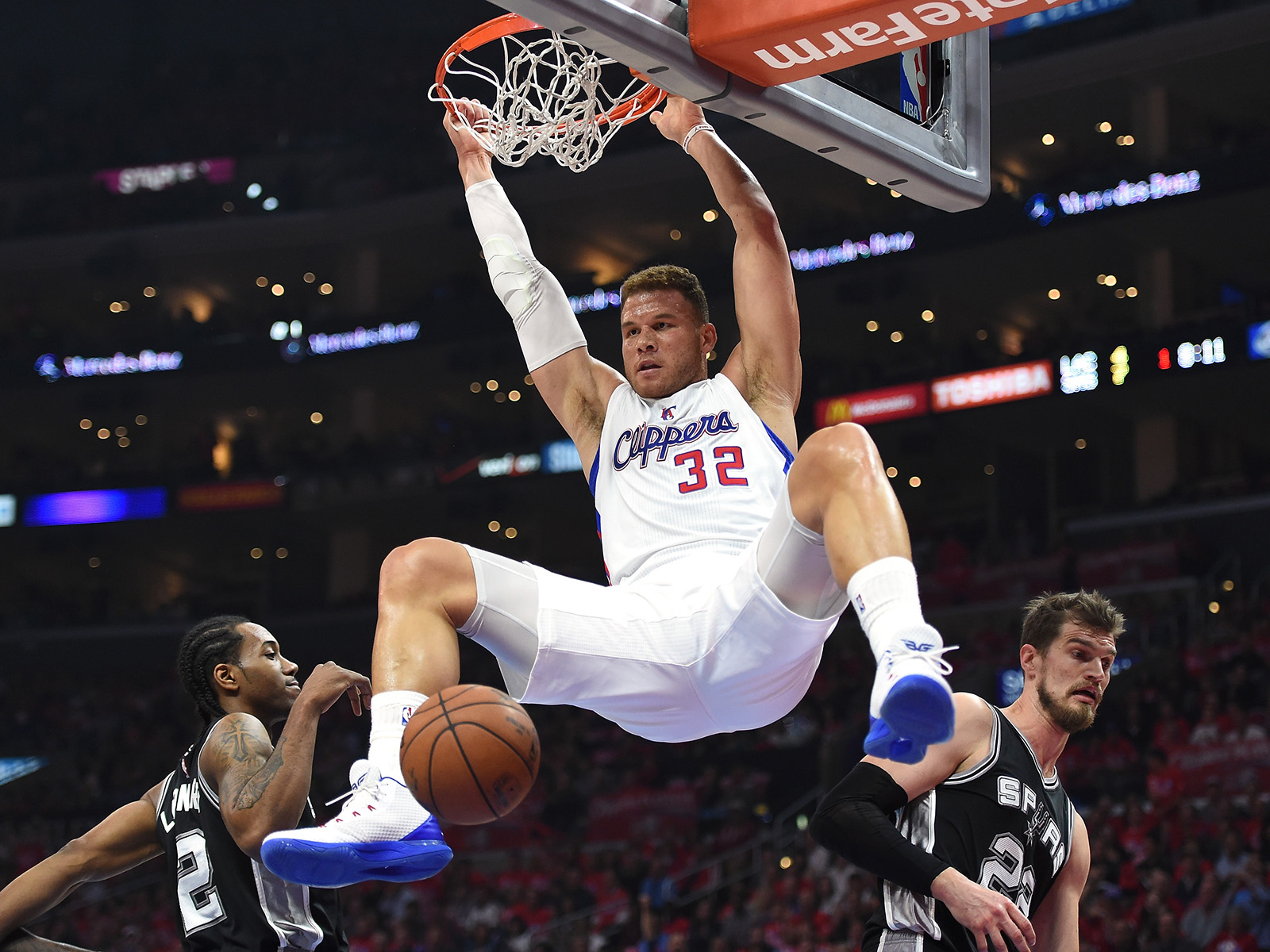 Blake Griffin hangs on the rim as Kawhi Leonard and the San Antonio Spurs look on.