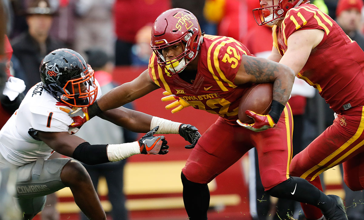 Running back David Montgomery #32 of the Iowa State Cyclones rushes for yards as linebacker Calvin Bundage #1 of the Oklahoma State Cowboys blocks in the first half of play at Jack Trice Stadium on November 11, 2017 in Ames, Iowa. (Photo by David Purdy/Getty Images)