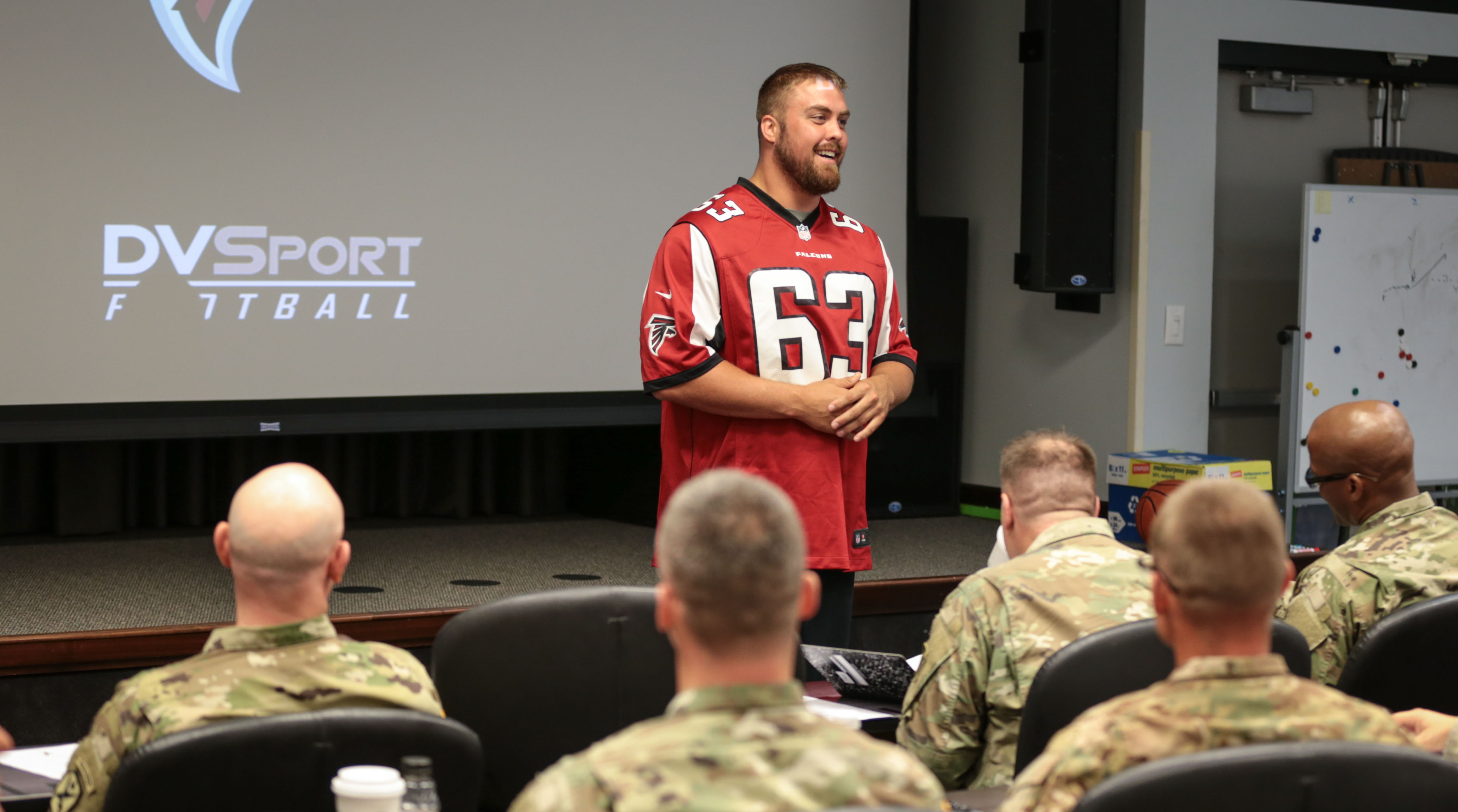 Falcons guard Ben Garland speaks to military servicemen.