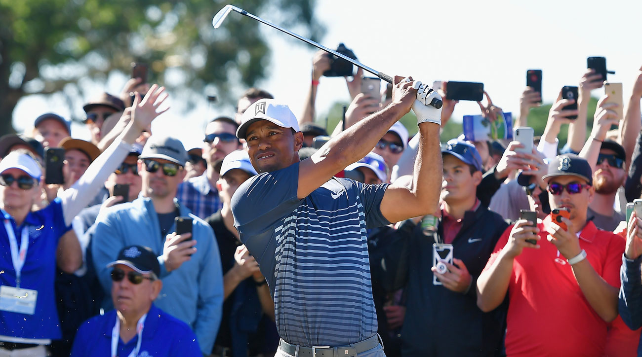 Tiger Woods plays a shot out of the rough on the 17th hole during the second round of the Farmers Insurance Open.