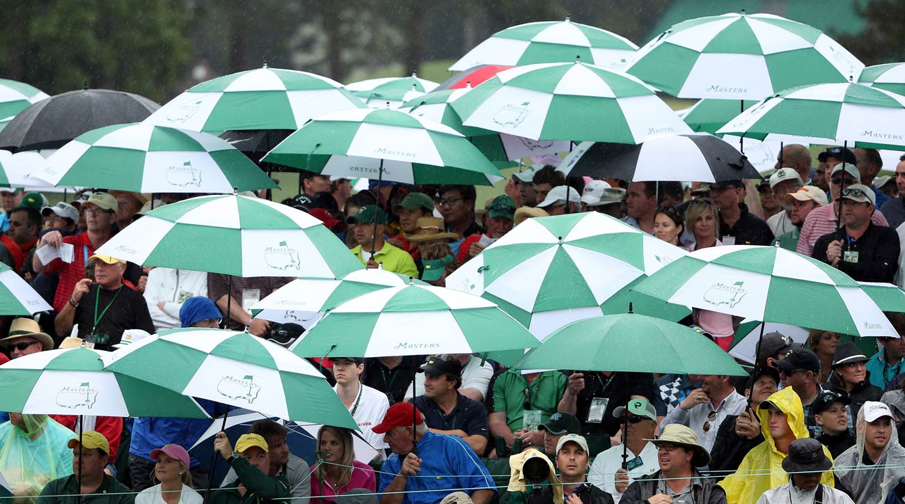 Patrons around the 18th green shelter from the rain during the final round of the 2013 Masters.
