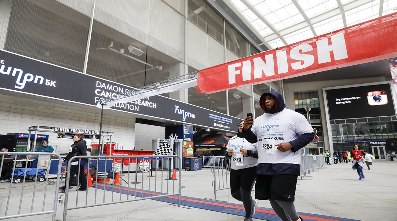 Devon Still and his wife Asha cross the finish line at the 10th annual Damon Runyon 5K on April 15, 2018. The event raised over $400,000 for cancer research.