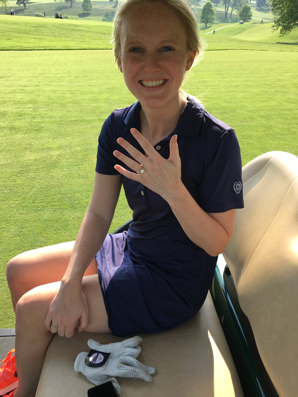 The blushing bride-to-be looks thrilled by both her hole-in-one AND her engagement.