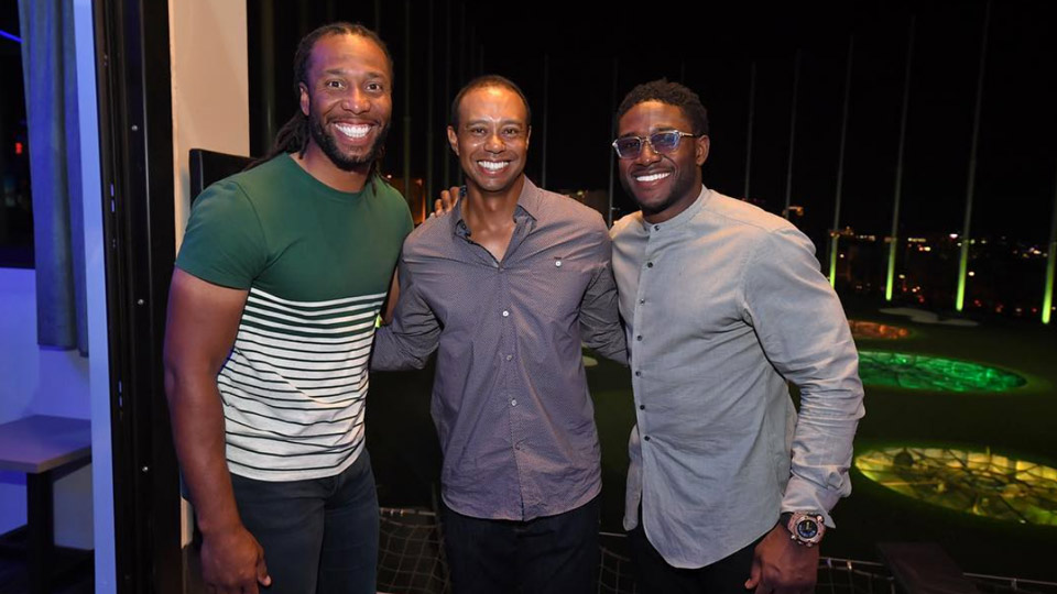 <p>Tiger poses with Larry Fitzgerald and Reggie Bush at Topgolf.</p>