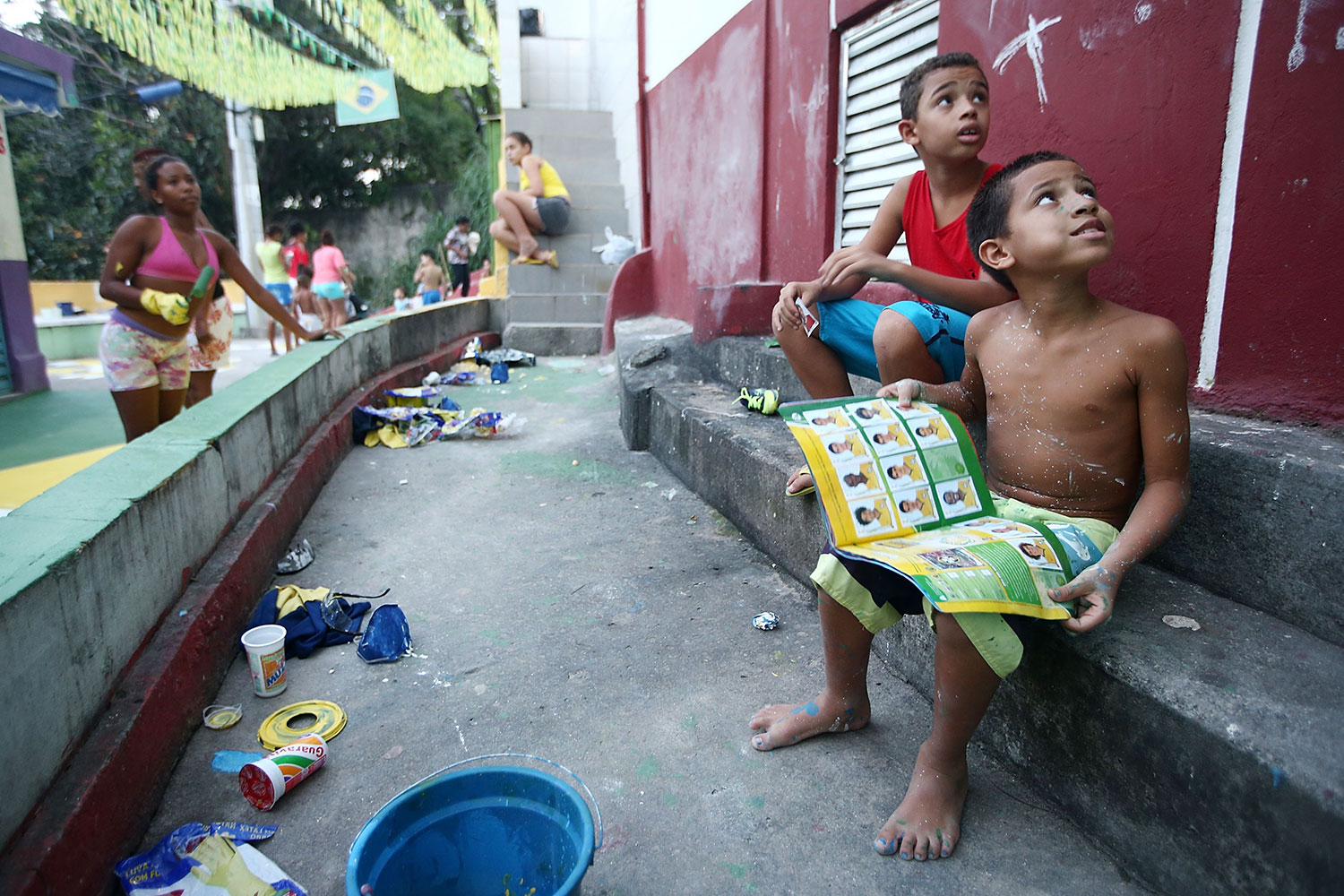 Rio de Janeiro, Brazil, 2014.  Brazilians gather while painting a section of the Santa Marta favela in Brazilian colors as a boy holds his Panini World Cup sticker album.