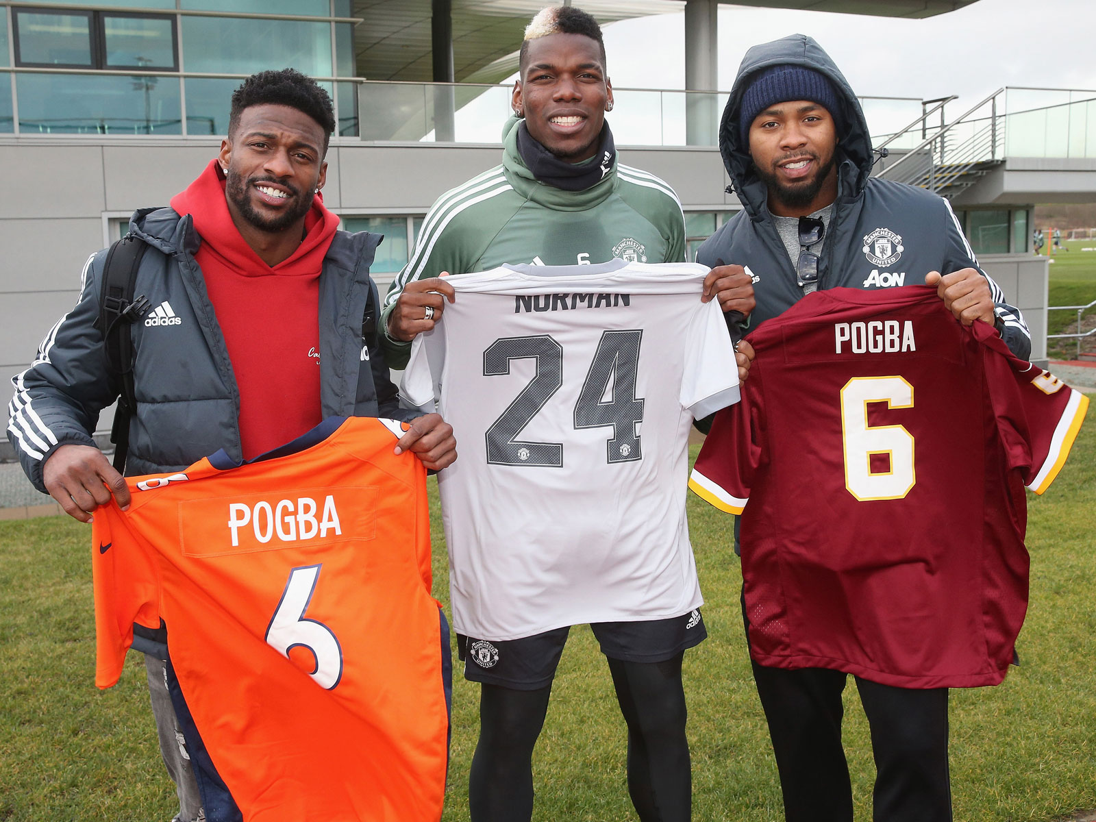 Emmanuel Sanders and Josh Norman pose with Paul Pogba at Manchester United's training ground