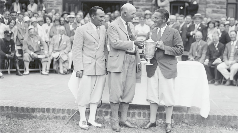 Al Espinosa looks on as Bobby Jones is presented with the U.S. Open trophy in 1929. Though Espinosa was beaten by 23 shots over 18 holes in the playoff against Jones, he would have won the championship under the new playoff rules.