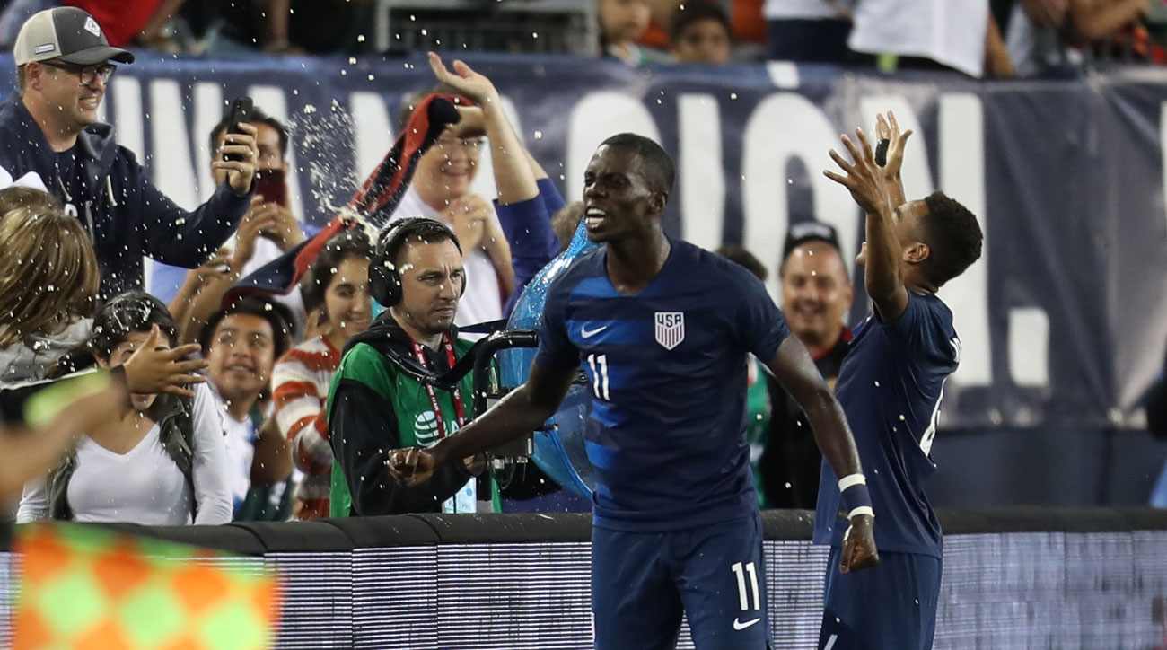 Tim Weah and Tyler Adams celebrate the USA's win over Mexico