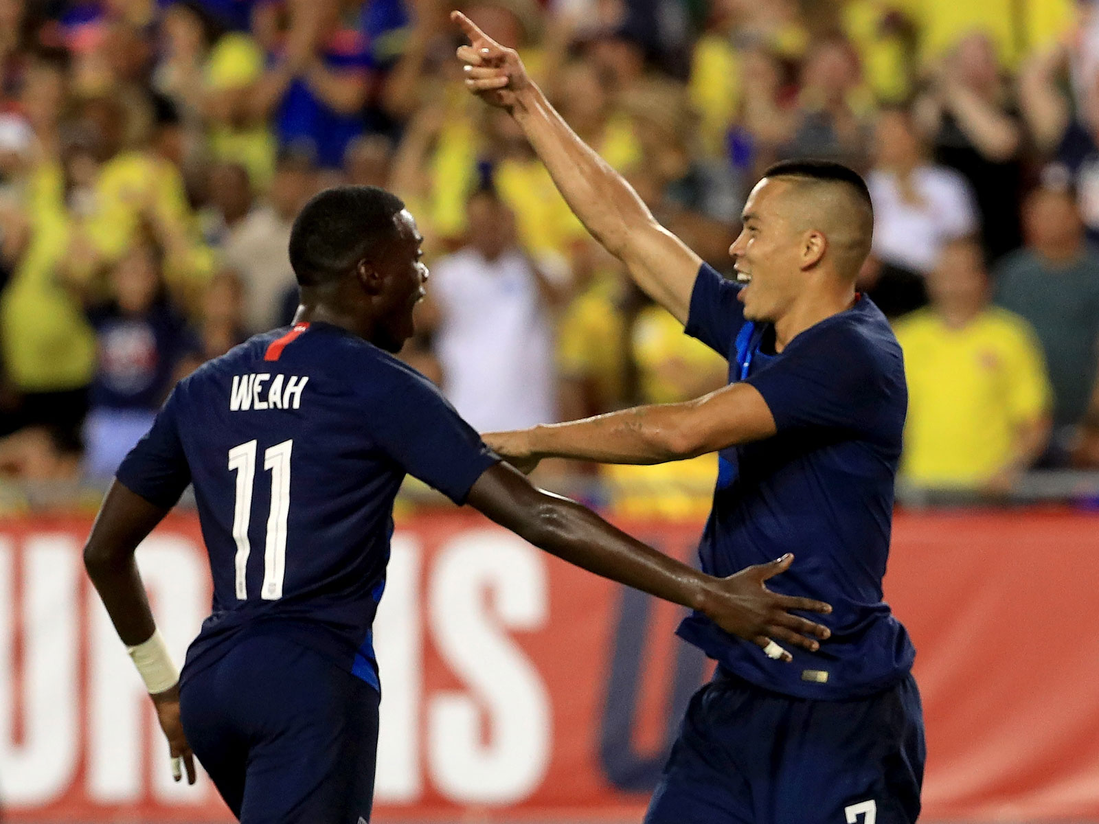 Tim Weah and Bobby Wood celebrate a goal vs. Colombia