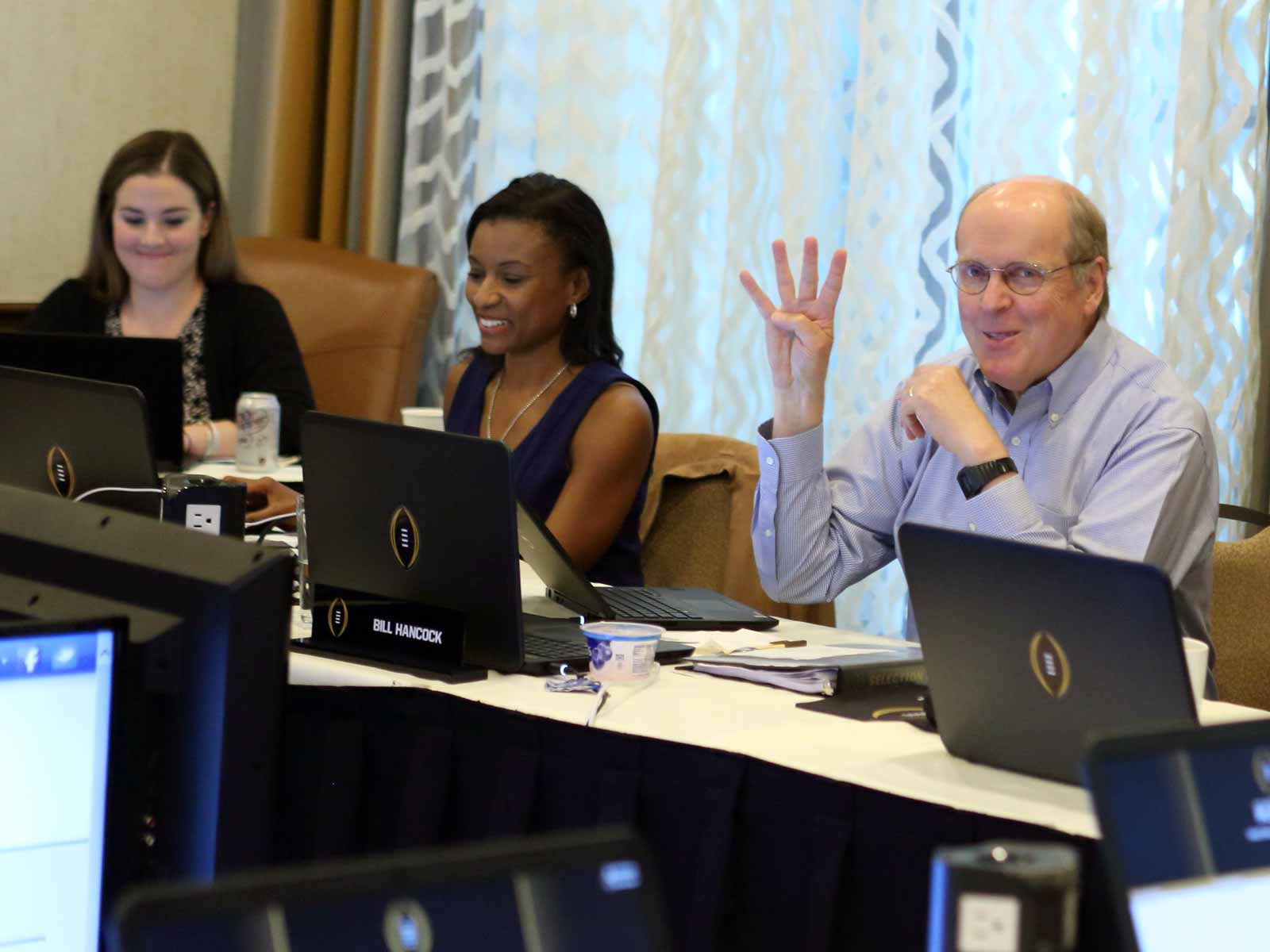 CFP executive director Bill Hancock sits next to Laila Brock during a committee meeting. In the background to the left is Gina Lehe's corner desk. A replacement sits in her seat. She was delivering her second daughter at the time of this meeting.