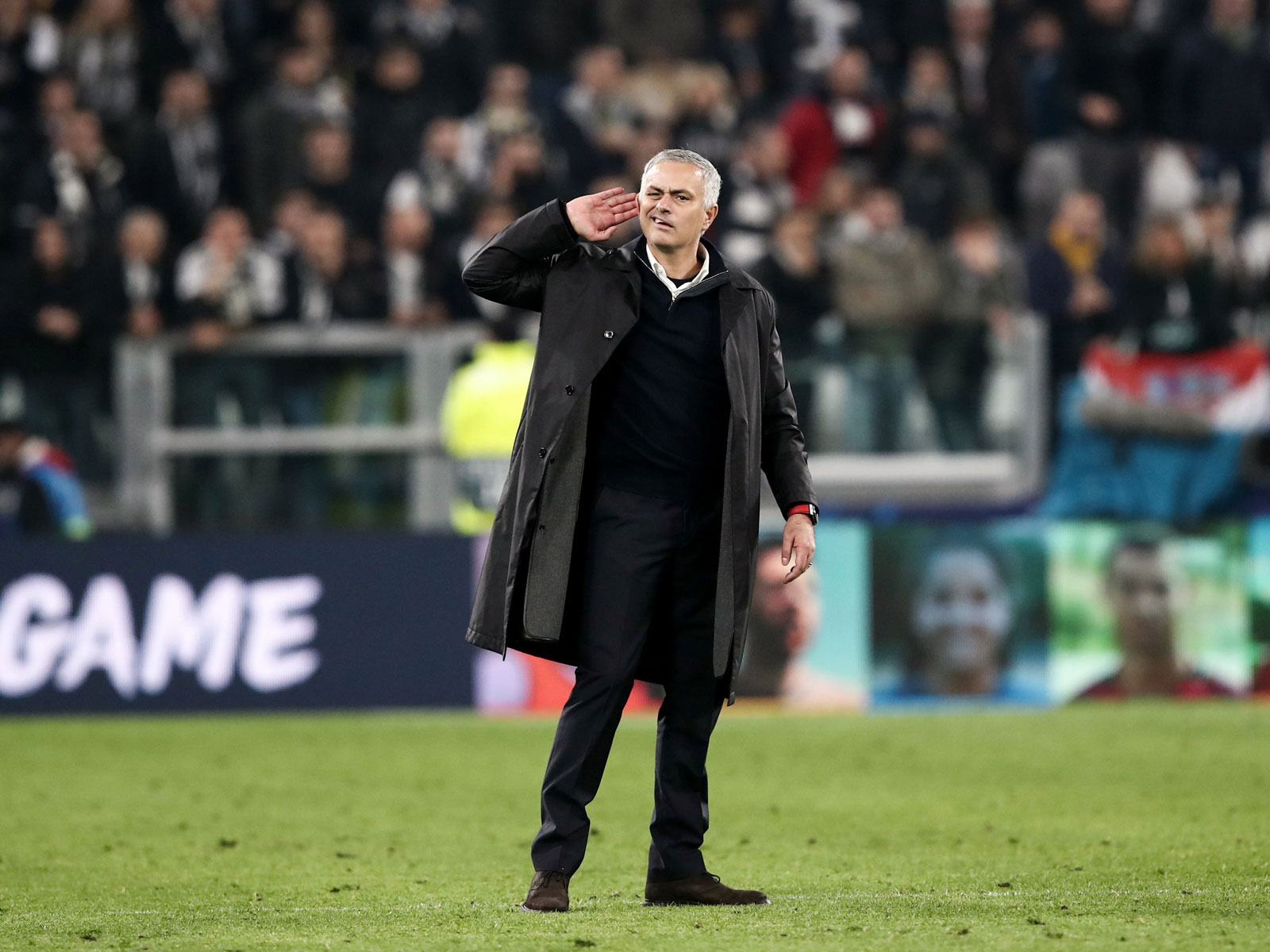 Jose Mourinho puts his hand to his ear to listen to the Juventus supporters