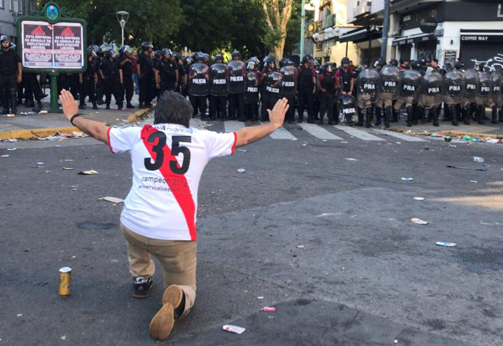 A River Plate fan confronts riot police at the Copa Libertadores final