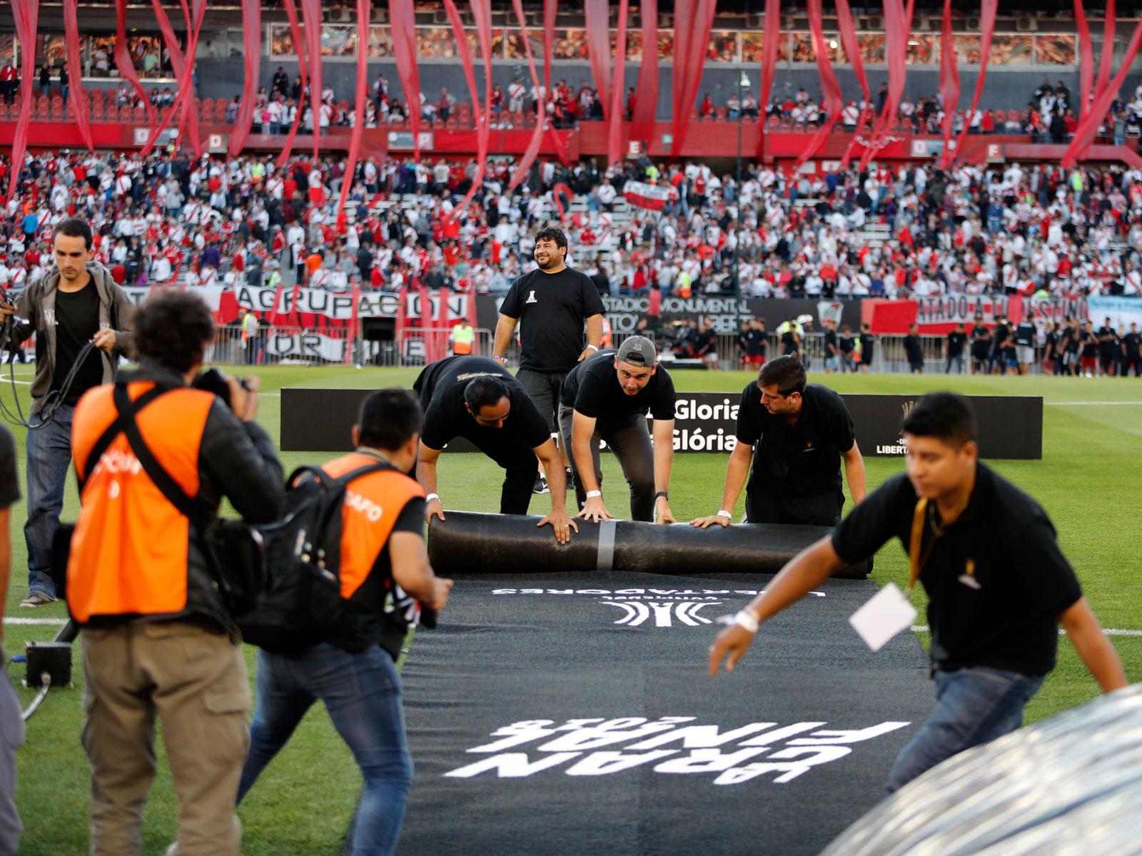 Officials close up shop at El Monumental after the postponement of the Copa Libertadores final