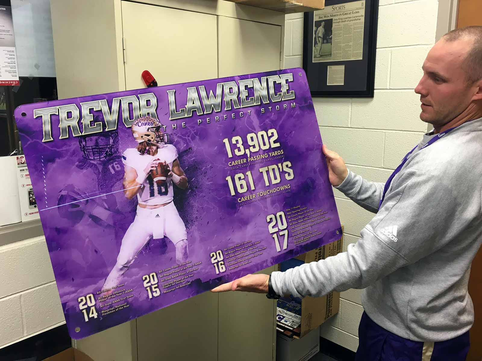 Cartersville High coach Joey King holds an illustration he had made of TrevorLawrence's accomplishments in four years as Cartersville's starting quarterback.