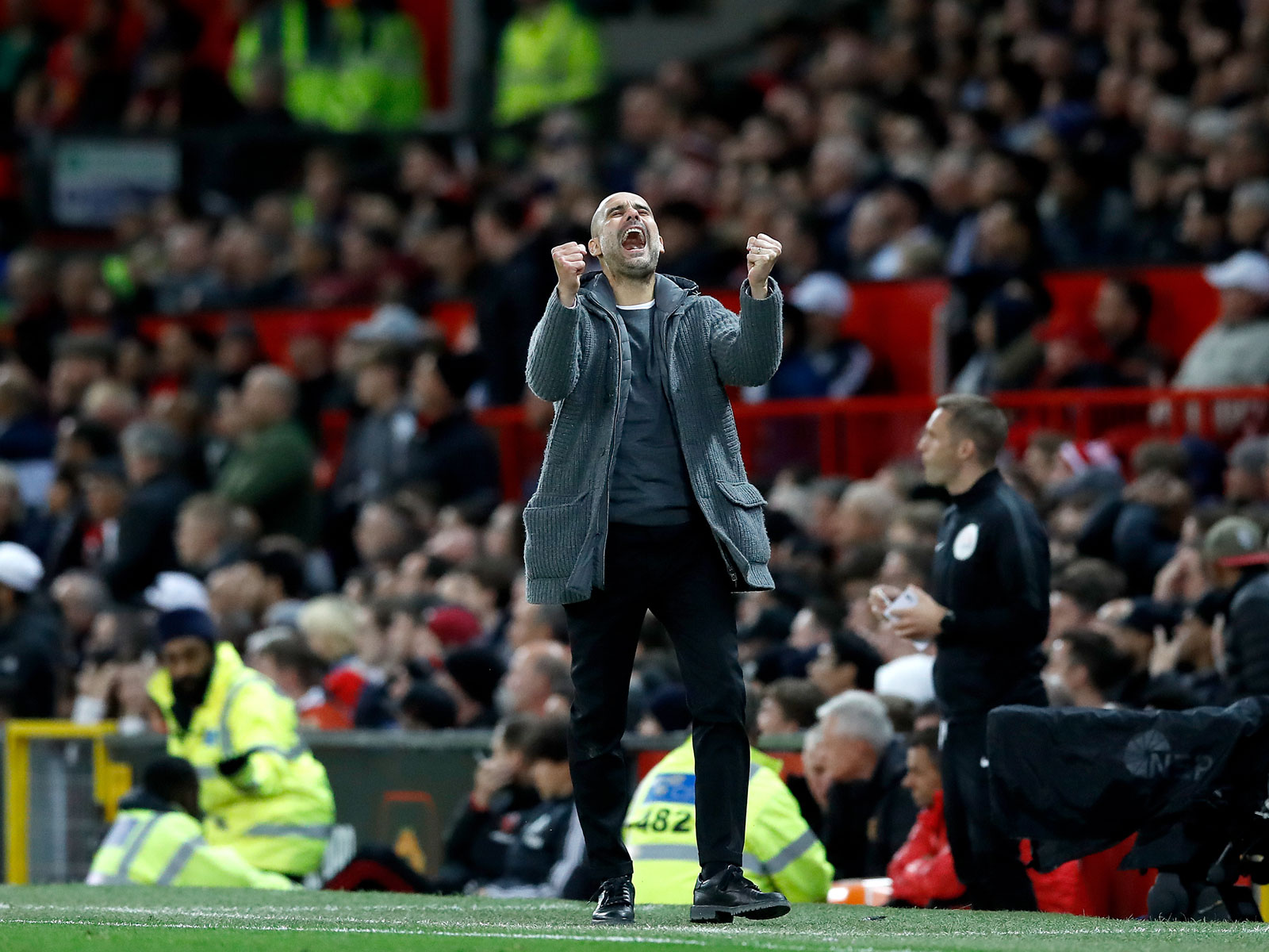 Pep Guardiola celebrates a goal in the Manchester Derby