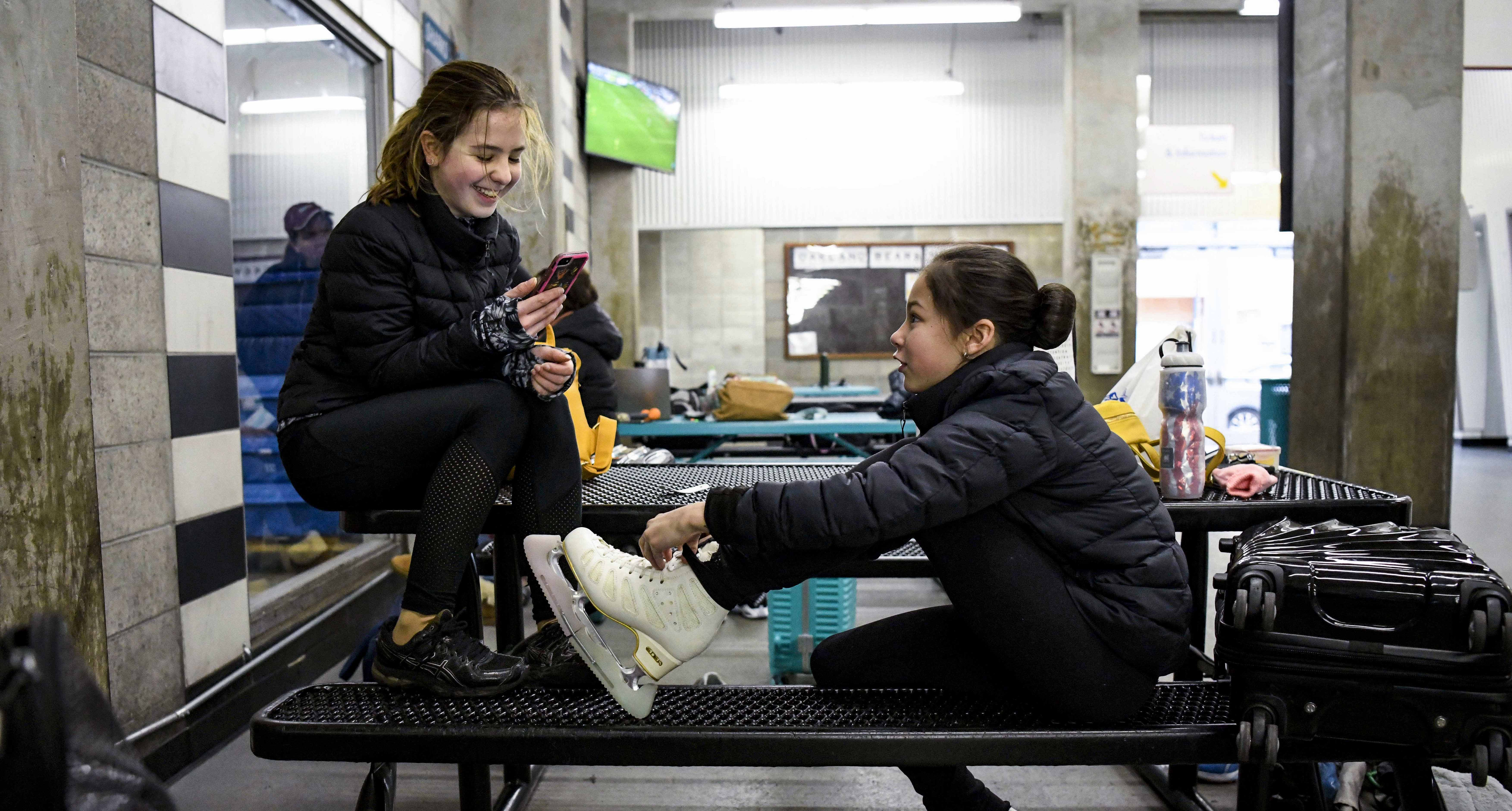 Alysa Liu laces up her skates before a practice session with her best friend Juliana Newton.