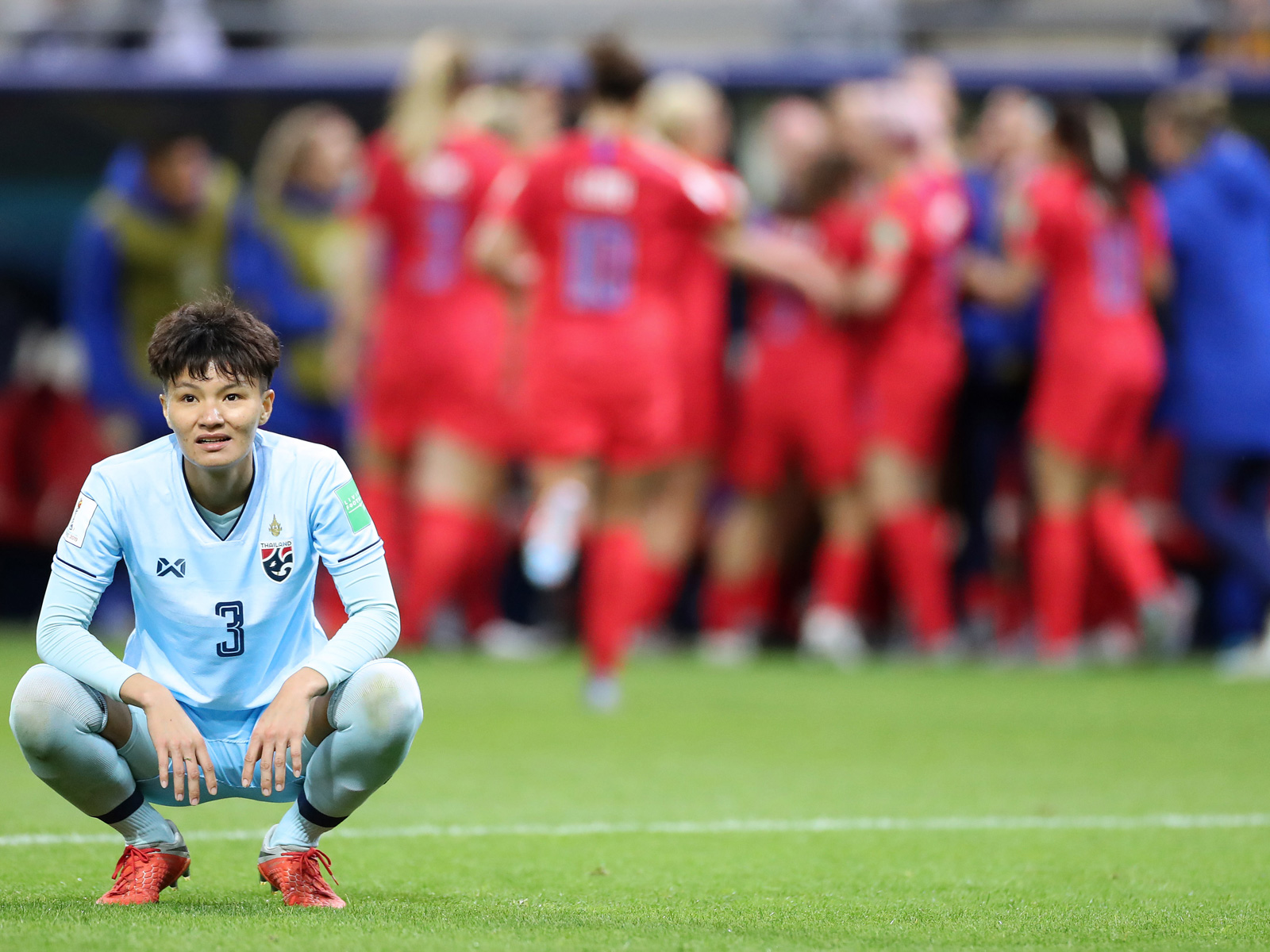 Natthakarn Chinwong crouches as the USA celebrates a goal at the Women's World Cup