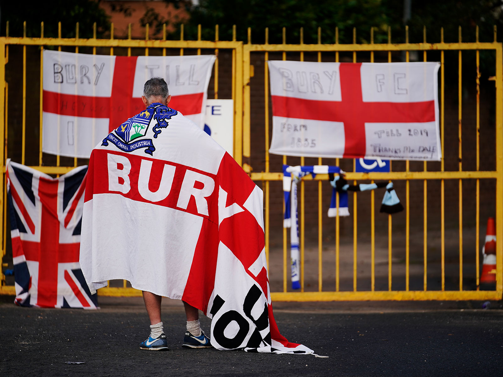 A Bury fan stands outside his club's stadium