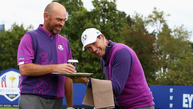 Europe team vice captain Padraig Harrington acts as a waiter for Thomas Bjorn of Europe during practice ahead of the 2014 Ryder Cup