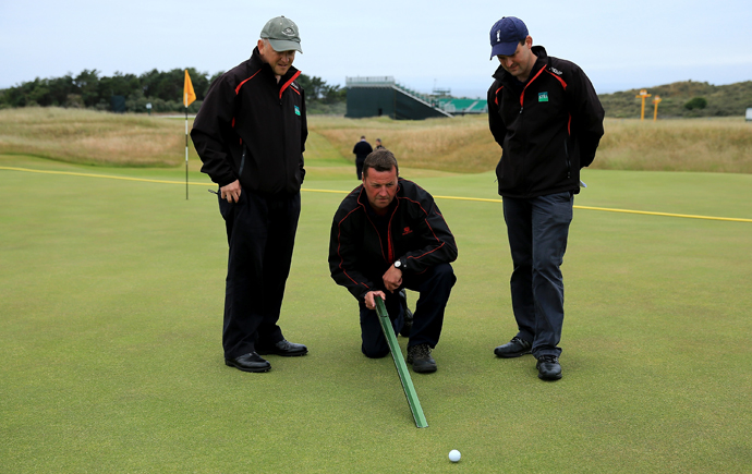 Muirfield course manager Colin Irvine and staff from STRI the R&A Agronomists check the pace of the greens with a Stimpmeter during a practice round prior to the 2013 Open Championship.