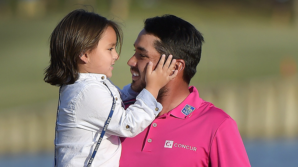 Jason Day exits the 18th green while holding his son Dash after winning the 2016 Players Championship.
