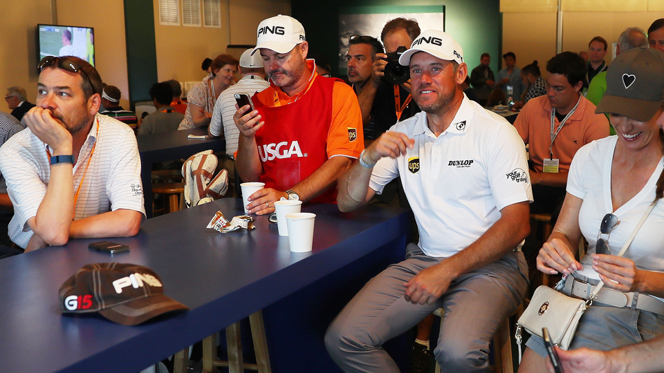 Lee Westwood (right in white) takes in England vs. Wales during a weather delay at the U.S. Open.