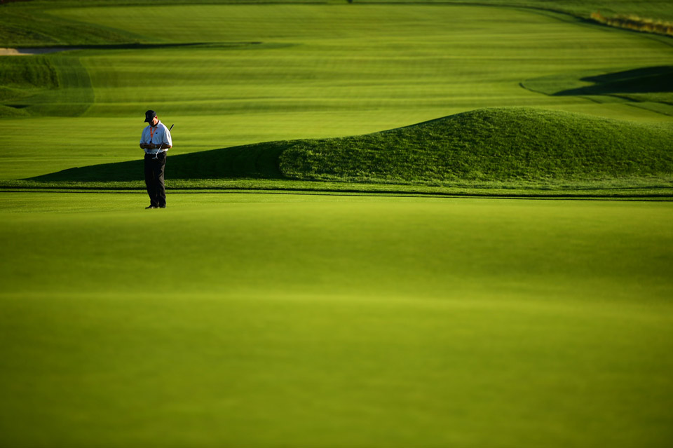 Mike Davis of the USGA inspects the course Saturday morning.