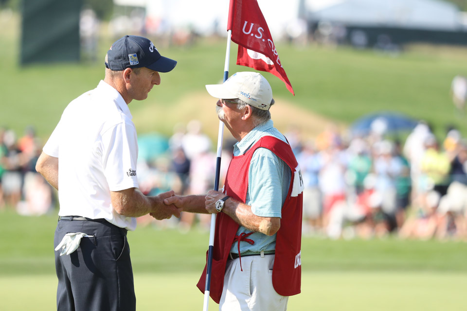 "Furyk shakes hands with his caddie Mike ""Fluff"" Cowan following his final round."
