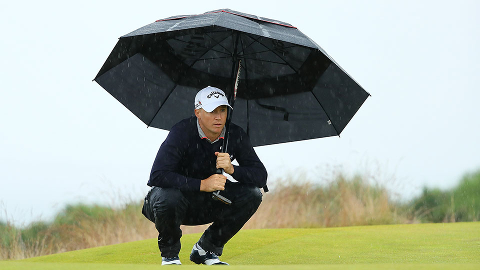 Alex Noren of Sweden holds an umbrella as he lines up a putt during the third round of the AAM Scottish Open at Castle Stuart Golf Links on July 9, 2016 in Inverness, Scotland.