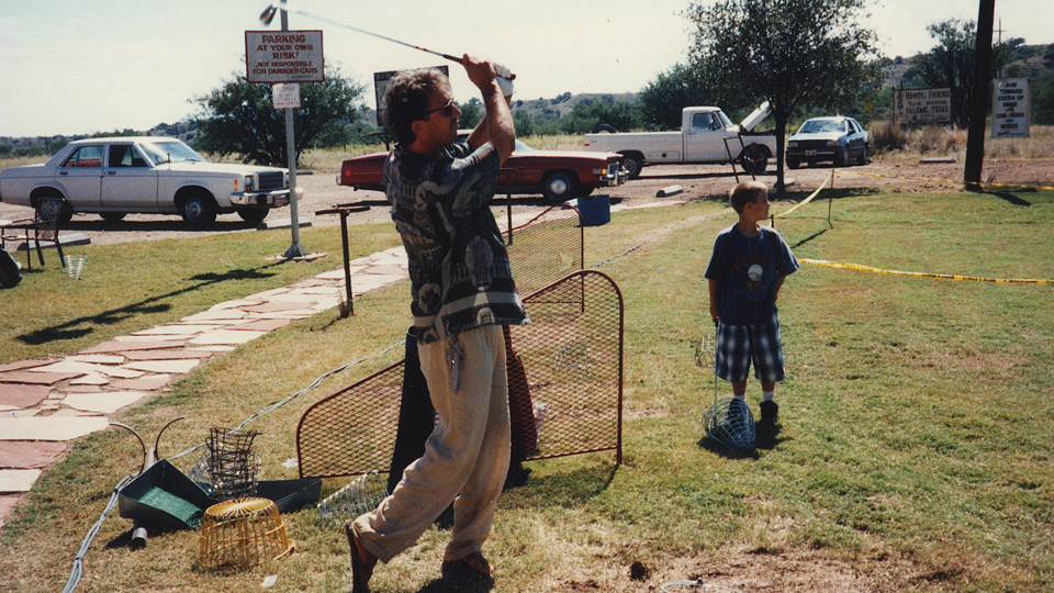 Kevin Costner takes swings on the range with his son, Joe, looking on.