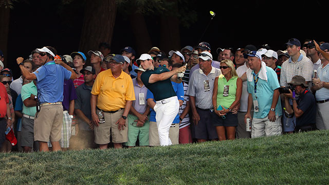 Rory McIlroy of Northern Ireland hits his second shot on the 18th hole as fans look on during the first round of the 2016 PGA Championship at Baltusrol Golf Club.