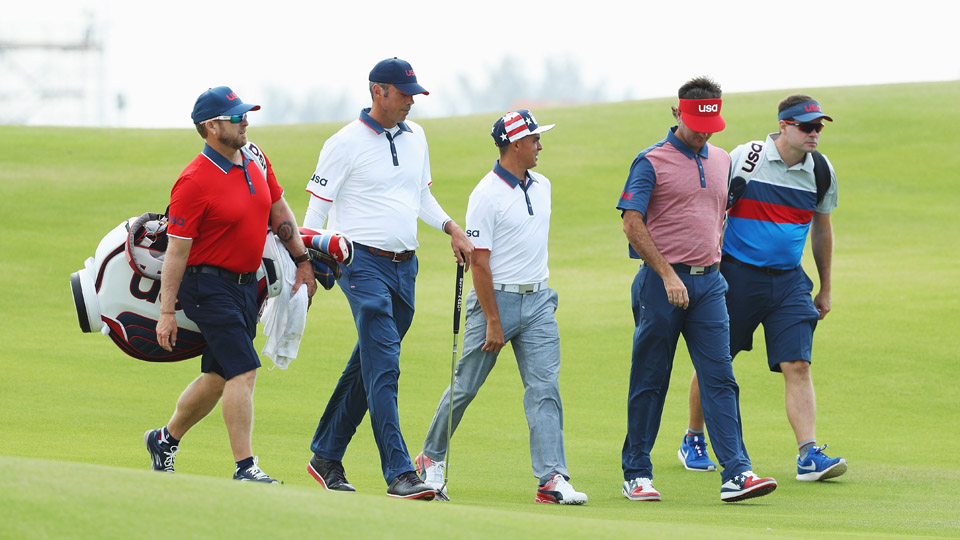 Matt Kuchar, Rickie Fowler and Bubba Watson walk down a fairway with their caddies during a practice round for the Olympics.