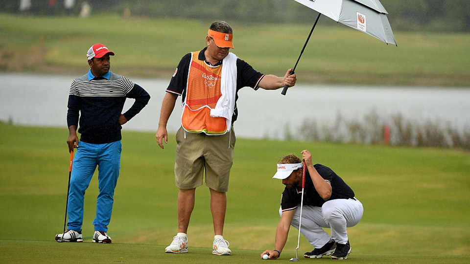 Joost Luiten is shielded from the rain by his caddie Michael Waite during the second round of the Olympics.