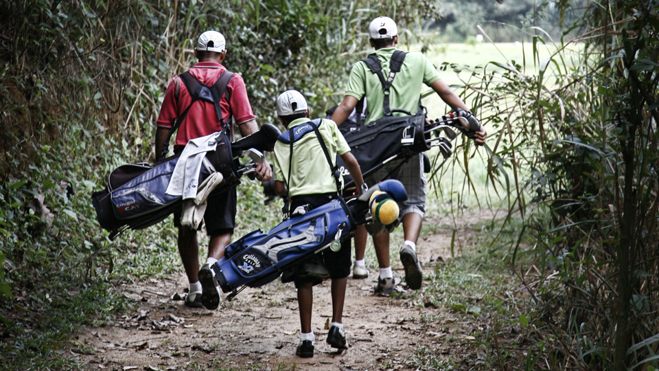 Three young boys walk to the 7th tee at Japeri Golf Club.